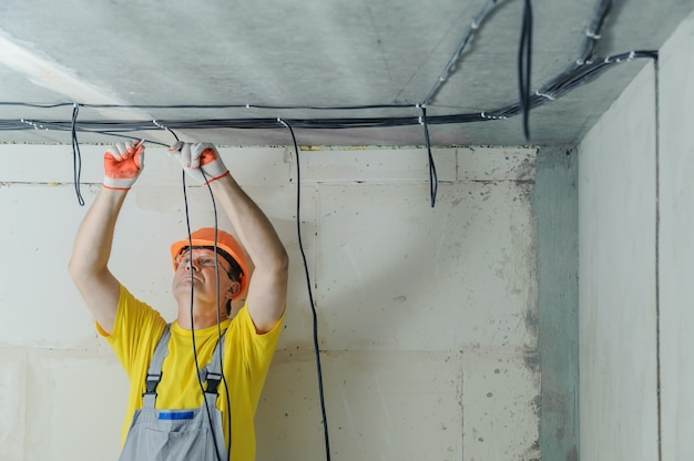 Электрик крепит к потолку электрические кабели.
