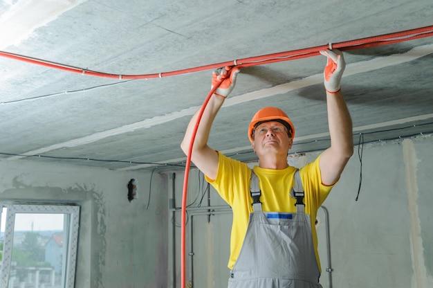 전기 기사가 전기 주름관을 천장에 고정하고 있습니다.