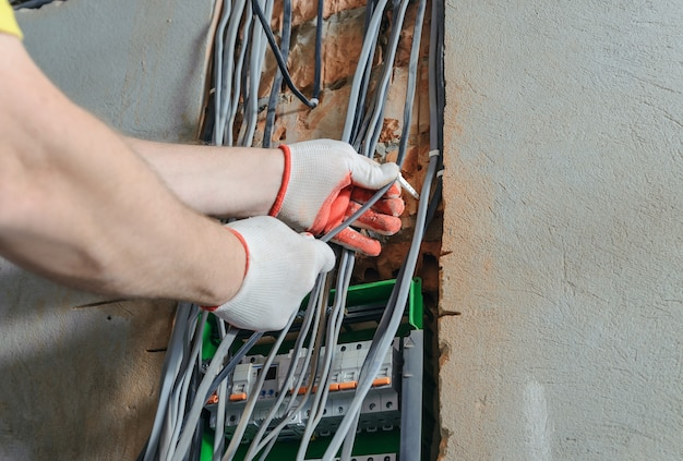 Электрик устанавливает электрические провода в коммутационный блок предохранителей.