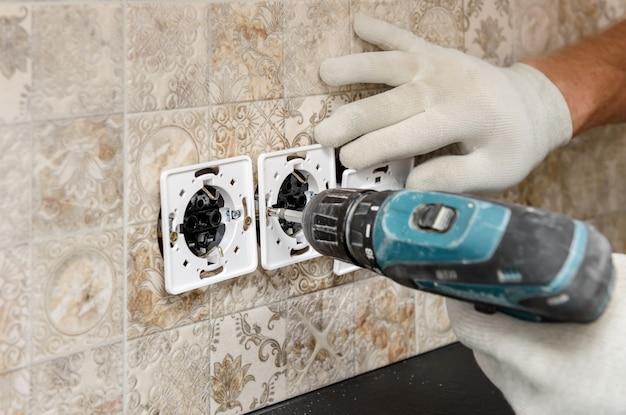 電気技師が壁のクローズアップにスイッチとソケットを取り付けています