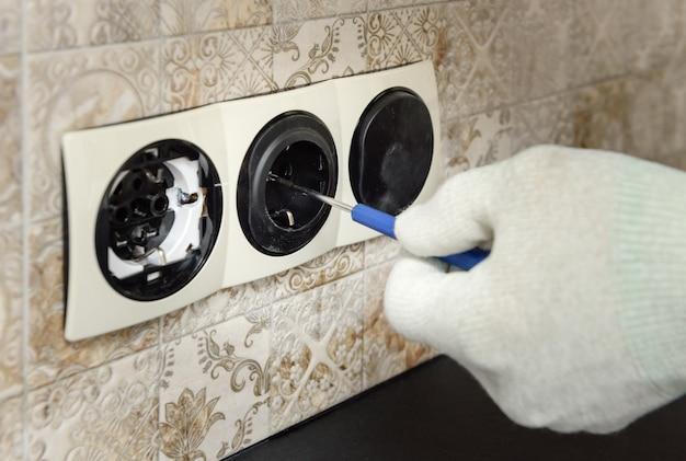 Электрик устанавливает на стене выключатели и розетки.