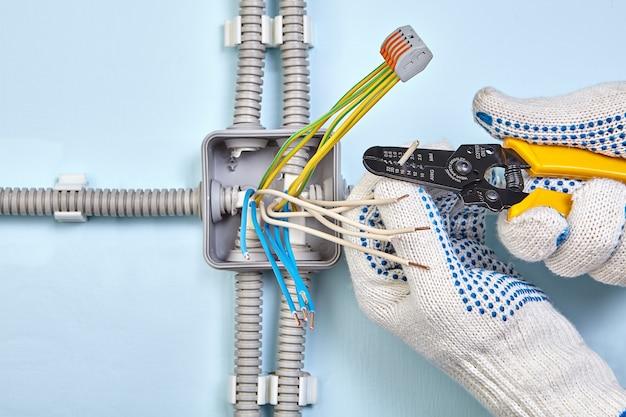 電気技師は、ワイヤーストリッパーツールを使用してワイヤー絶縁体を剥がしています。