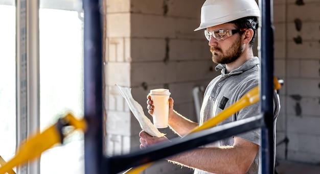 Электрик изучает строительный чертеж с кофе в руке.