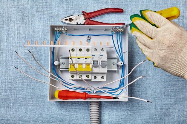 Электрик прикрепляет провода к клеммной колодке для нейтрального тока.