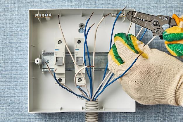 電気技師はワイヤーストリッパーを使用して、銅を切断せずに絶縁体を除去します。サーキットブレーカ付きの家庭用電気パネルの設置。家庭用電気配線にはヒューズを使用してください。