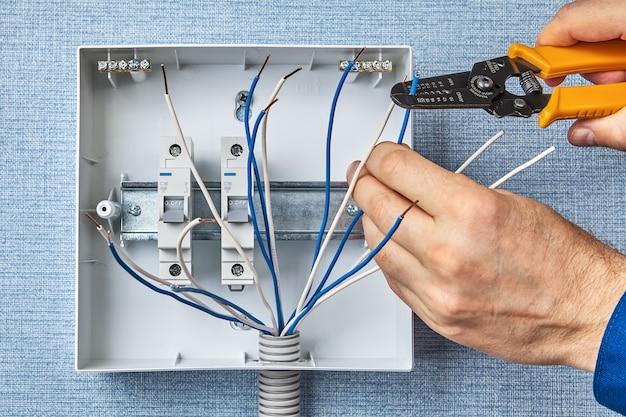 Электрик использует инструмент для снятия изоляции с электрических проводов при установке блока предохранителей.