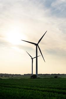 영국의 흐린 푸른 하늘을 배경으로 푸른 들판에서 전기를 생산하는 풍차