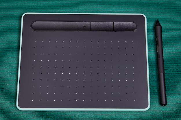 개인용 컴퓨터 용 전자 입력 장치, 스타일러스 펜이있는 그래픽 태블릿이 테이블 위에 놓여 있습니다.