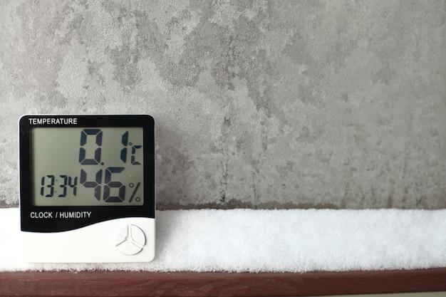 На снегу установлен электронный термометр и гигрометр для контроля температуры и влажности. показатель влажности указывается на гигрометре прибора.