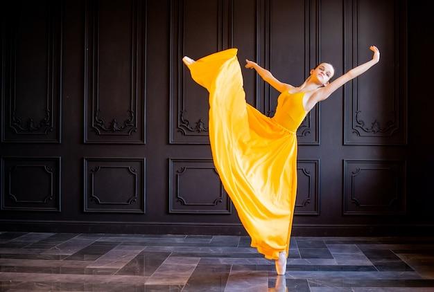포인트 슈즈의 우아한 발레리나가 어두운 회색 배경에 흐르는 노란색 천으로 춤을 춥니 다.