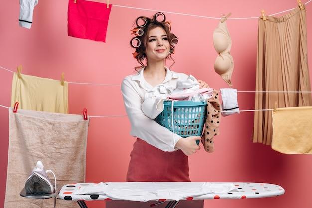 頭にカーラーを付けたエレガントで美しい主婦は、服のバスケットを持っており、服の後ろにひもを掛けています。