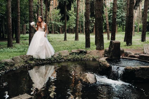 Элегантная невеста в белом платье и перчатках с букетом стоит у ручья в лесу, наслаждаясь природой. модель в свадебном платье и перчатках в природном парке. беларусь
