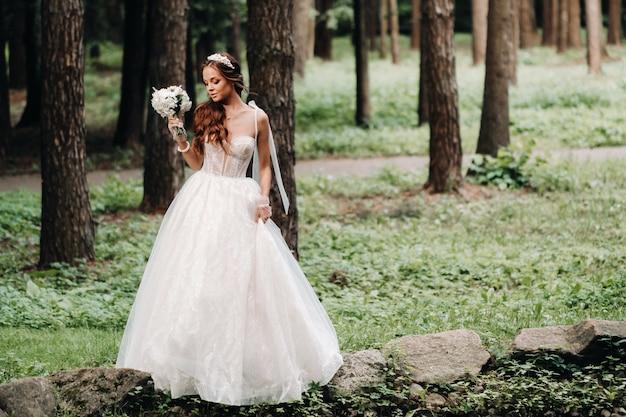 白いドレスと花束を持った手袋をはめたエレガントな花嫁が森の小川のそばに立って、自然を楽しんでいます。結婚式のドレスと自然公園の手袋のモデル。ベララス
