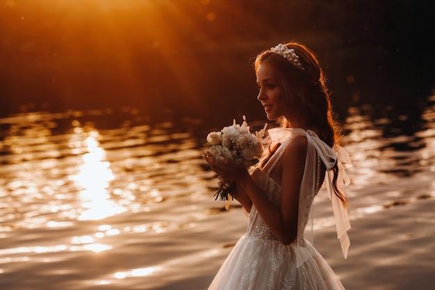 白いドレスと手袋をはめたエレガントな花嫁が花束を持って公園の川のそばに立って、日没時に自然を楽しんでいます。自然公園の結婚式のドレスと手袋のモデル。ベララス