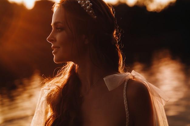白いドレスを着たエレガントな花嫁は日没時に自然を楽しんでいます。公園の自然の中でウェディングドレスのモデル。ベラルーシ