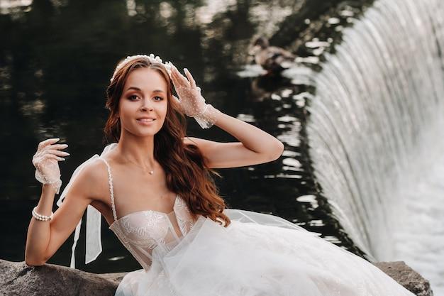 Элегантная невеста в белом платье, перчатках и босой ноге сидит у водопада в парке, наслаждаясь природой. модель в свадебном платье и перчатках в природном парке. беларусь