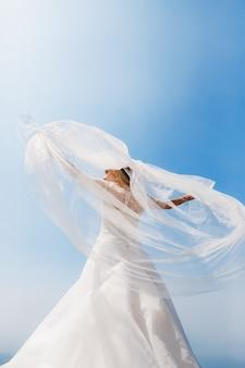 우아한 신부가 팔을 뻗고 바람이 베일을 불고 서 있습니다.