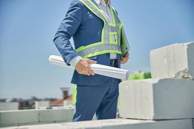 건축 현장에 서있는 그의 그림을 가진 우아한 토목 기사