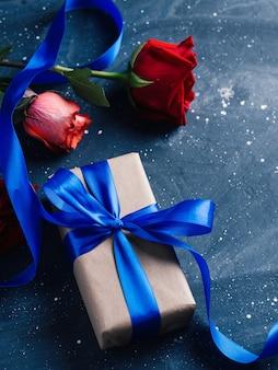 青いリボンで結ばれたエレガントなギフトボックス、バラの花束と暗いテーブルの上の赤ワインのボトル、ロマンチックな夜。バレンタインデーギフト Premium写真