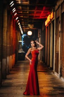 マルセイユの夜の街の路上で赤いイブニングドレスを着たエレガントな女の子。フランスの赤いイブニングドレスを着た女性。