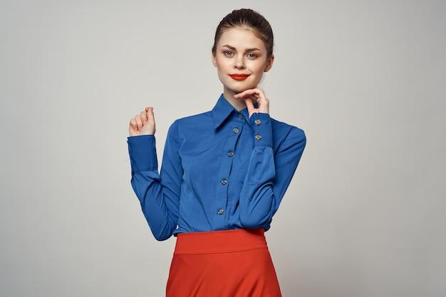 青いシャツを着たエレガントな女性が彼女の手で身振りで示す