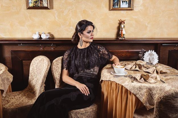 Элегантная дама в вечернем платье за столиком в кафе. интерьер ресторана.