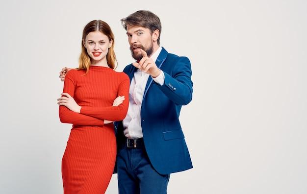 Элегантный мужчина в костюме и женщина в красном платье на световой рекламе.