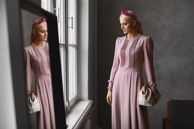 지갑을 유지하는 분홍색 이브닝 드레스를 입고 거울 근처의 빈티지 인테리어에서 포즈를 취하는 완벽한 메이크업으로 우아한 모델 여성