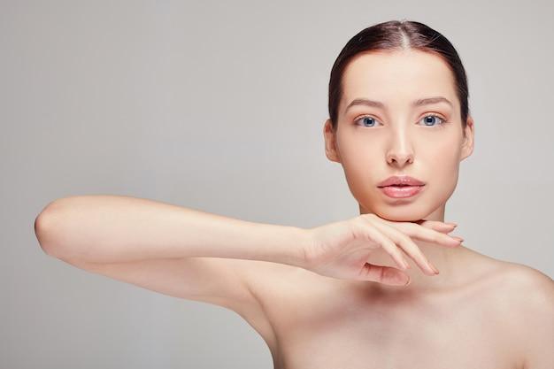 Элегантная утонченная красивая женщина с пухлыми губами, темными волосами и сияющей чистой нежной кожей