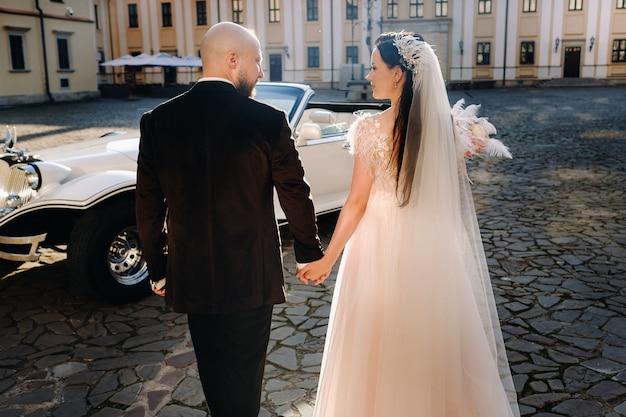 城の中庭で優雅な結婚式のカップルがレトロな車の近くで手をつないで歩く