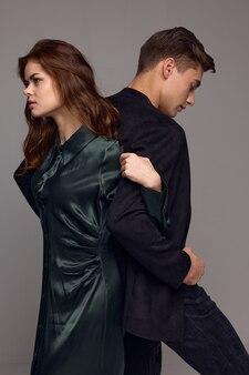 Элегантная женщина держит за руку мужчину в костюме на сером пространстве спиной друг к другу
