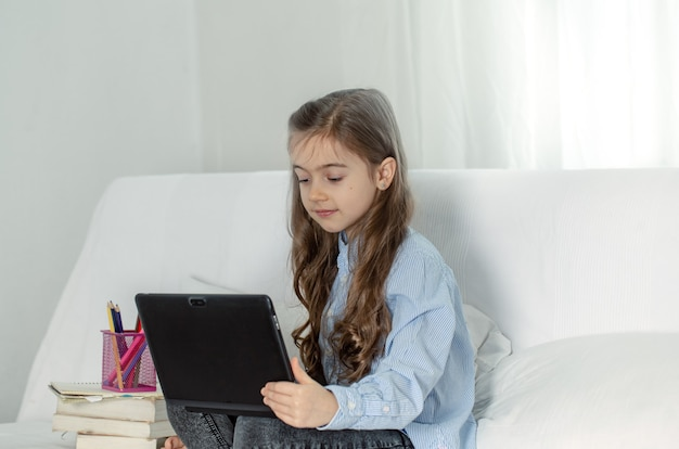 Ученица начальной школы сидит дома на диване с ноутбуком на онлайн-уроке во время карантина из-за пандемии коронавируса.