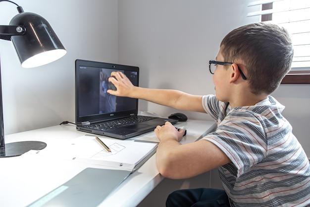 Ученик начальной школы сидит за партой перед ноутбуком и общается с другом по видеосвязи в интернете, дома.