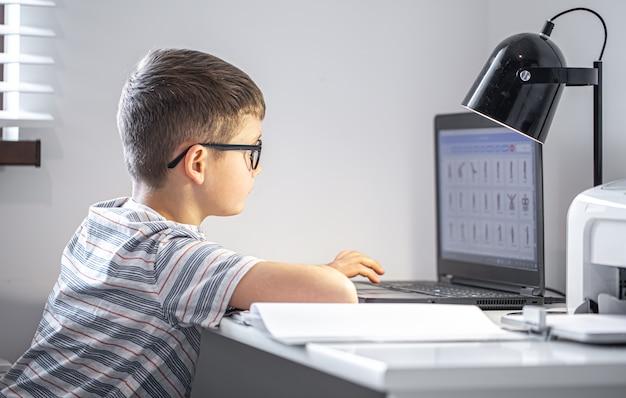 Ученик начальной школы в очках сидит за столом с ноутбуком, делает домашнее задание онлайн.