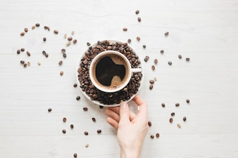 An elevated view of a person's hand holding saucer with coffee beans and cup of coffee