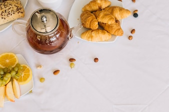 An elevated view of baked croissant; fruits; tea and dryfruits on white tablecloth