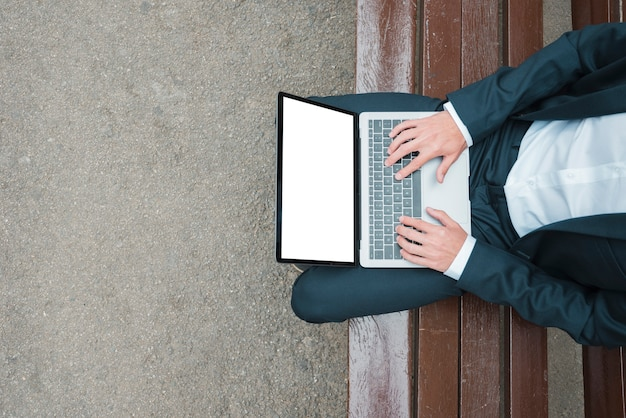 ノートパソコンに入力するベンチに座っている実業家の高架ビュー