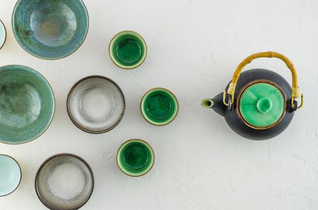 Поднятый вид пустых чашек чая с чайником, изолированных на белом фоне