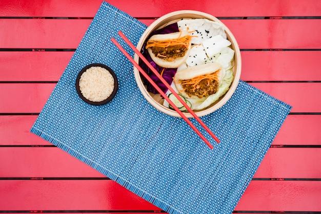 빨간색 테이블 위에 파란색 플레이스 매트에 플랫 찐 빵의 높은보기