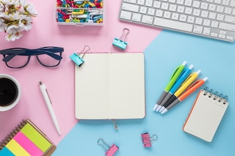 An elevated view of office supplies on dual pink and blue background