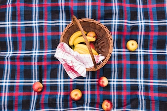 An elevated view of picnic basket with bananas and apples on blanket