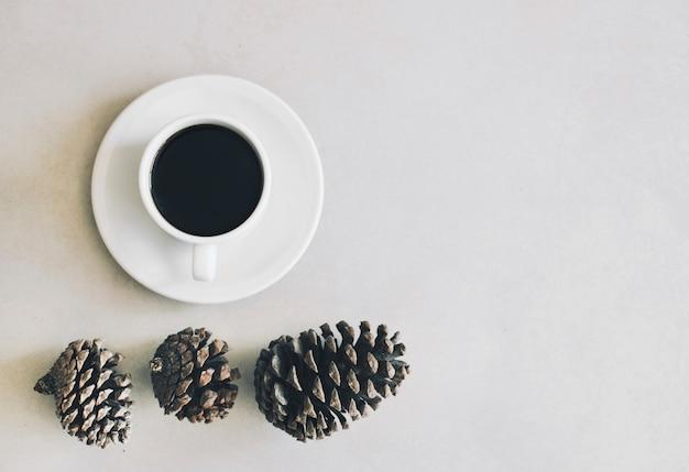 Поднятый вид сосновых шишек и чашка кофе с блюдцем на белом фоне