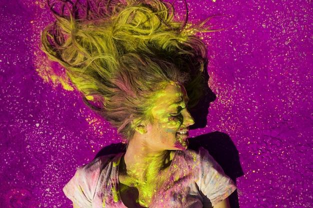 Поднятый вид улыбающейся женщины, покрытой порошком цвета холи
