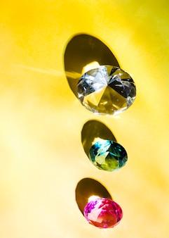 Повышенный вид белого; зеленый; и розовый бриллиант на желтом фоне