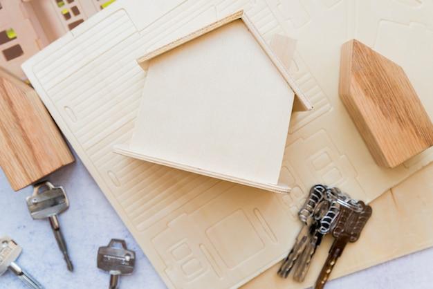 Поднятый вид деревянной миниатюрной модели дома с ключами