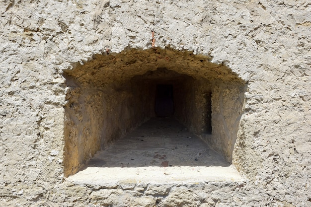 오래된 요새나 성의 두꺼운 벽에 총을 쏘기 위한 embrasure. 거친 돌로 덮인