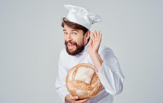 Эмоциональный повар в легкой одежде и головном уборе с буханкой хлеба в руке.