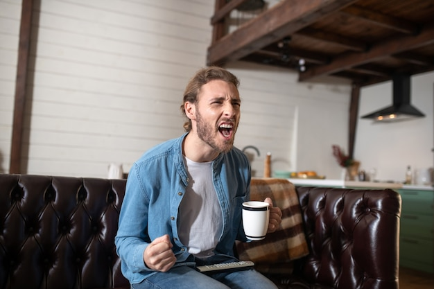 テレビを見ながら大声で叫ぶ感情的な男
