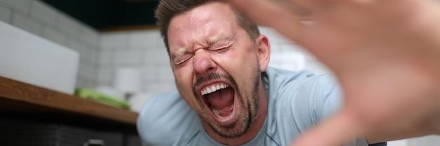 Эмоциональный мужчина сидит в туалете и кричит от боли