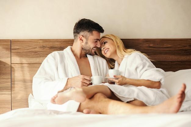 Эмоциональный момент перед поцелуем. солнечное утро в гостиничном номере, мужчина и женщина пьют кофе и чай, не выходя из халата и теплой постели. любовь, цель отношений, близкие отношения